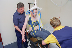 Carers using ceiling hoist to assist disabled man to transfer from bed to shower chair,