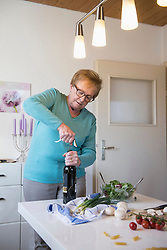 Old woman opening a bottle of red wine in the kitchen