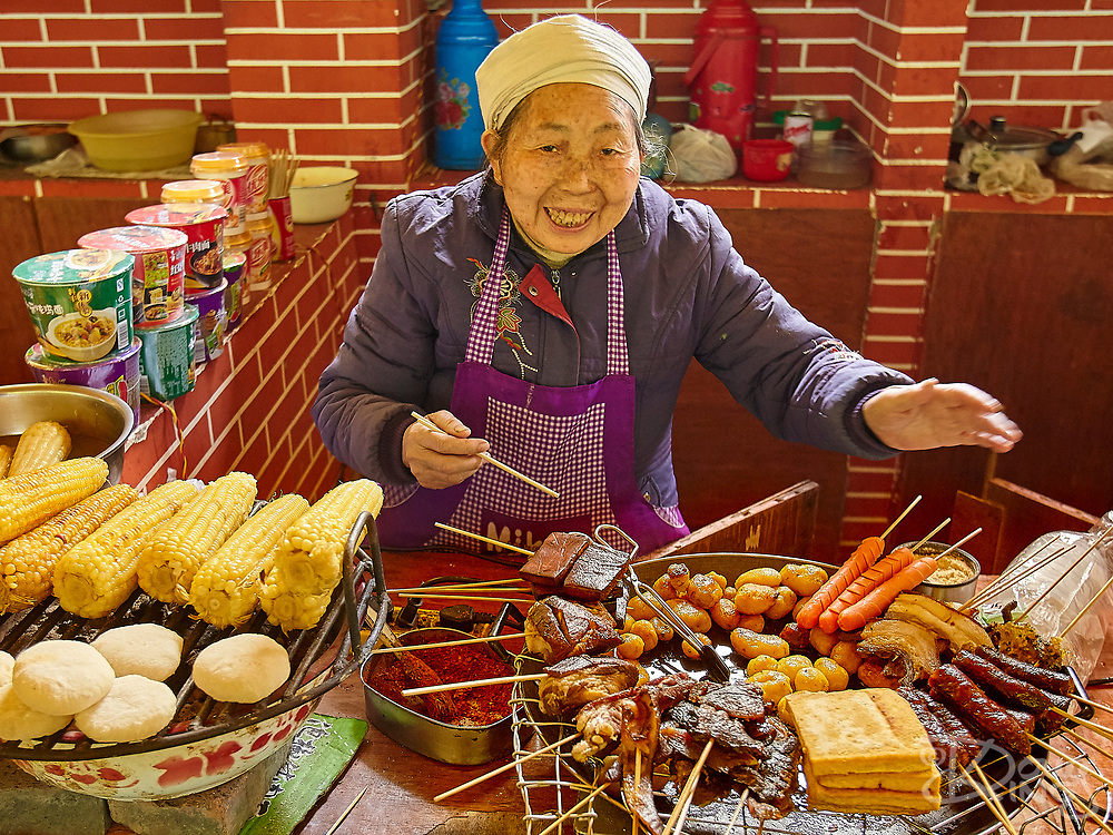 An elderly lady invites you to try her street food barbecue, corn on the cob, or dumplings in Chongqing Province, Southern China.