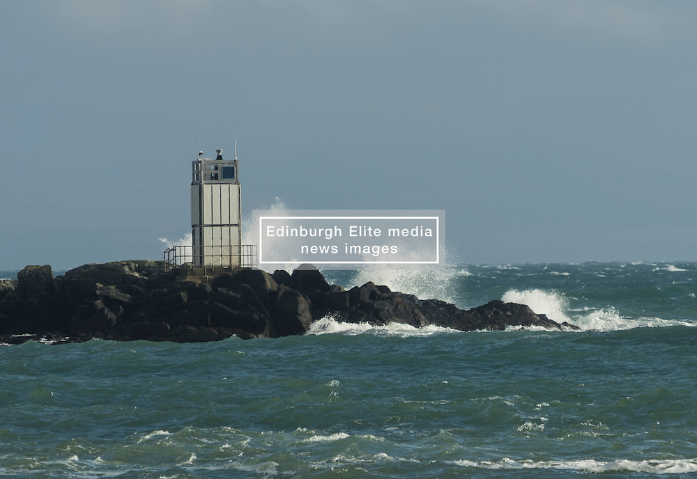 Strong winds hit the West Coast of Scotland. The ferries between the Southern Hebrides and the Scottish mainland have been cancelled as Easterly winds in excess of 40mph make the crossing impossible.<br /> <br /> Pictured: The lighthouse on Eilean nan Gabhar at the harbour into Craighouse, Jura is battered by waves.