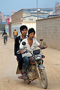 Two men ride though a construction zone on a motorbike in Longhua,  a city under construction in Shenzhen.