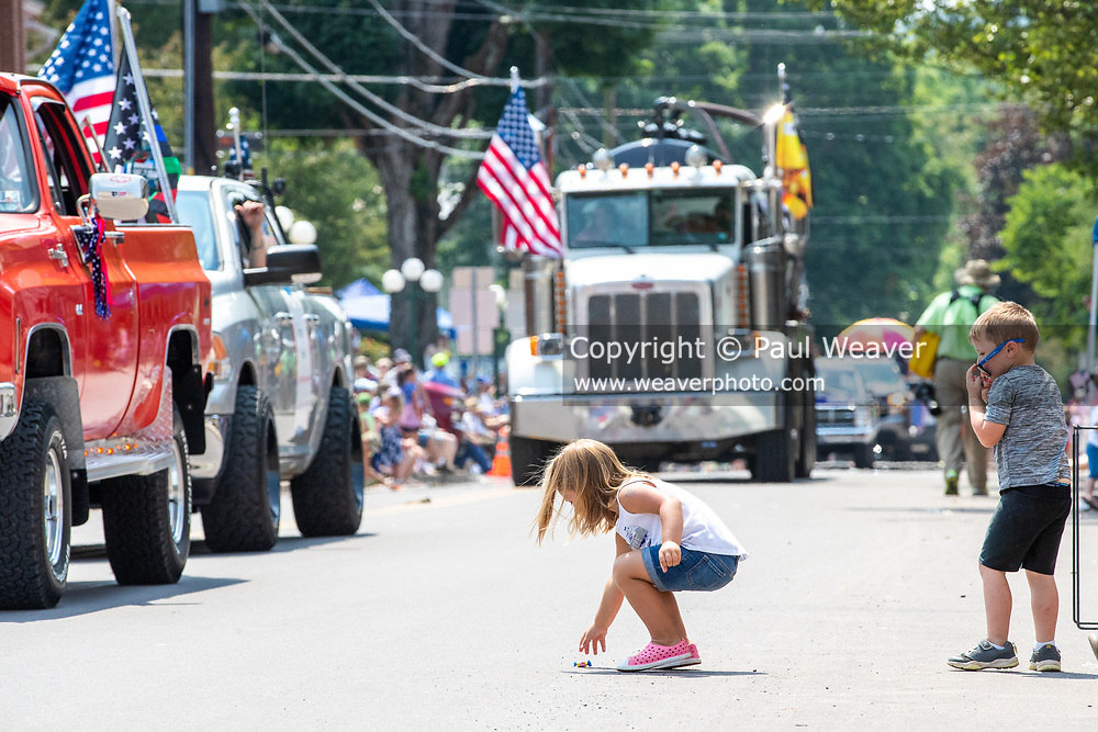 A child picks up a piece of candy from the street during the Independence Day parade in Millville, Pennsylvania on July 5, 2021.