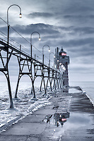 Tho South Haven light reflects brightly in an unfrozen pool of water