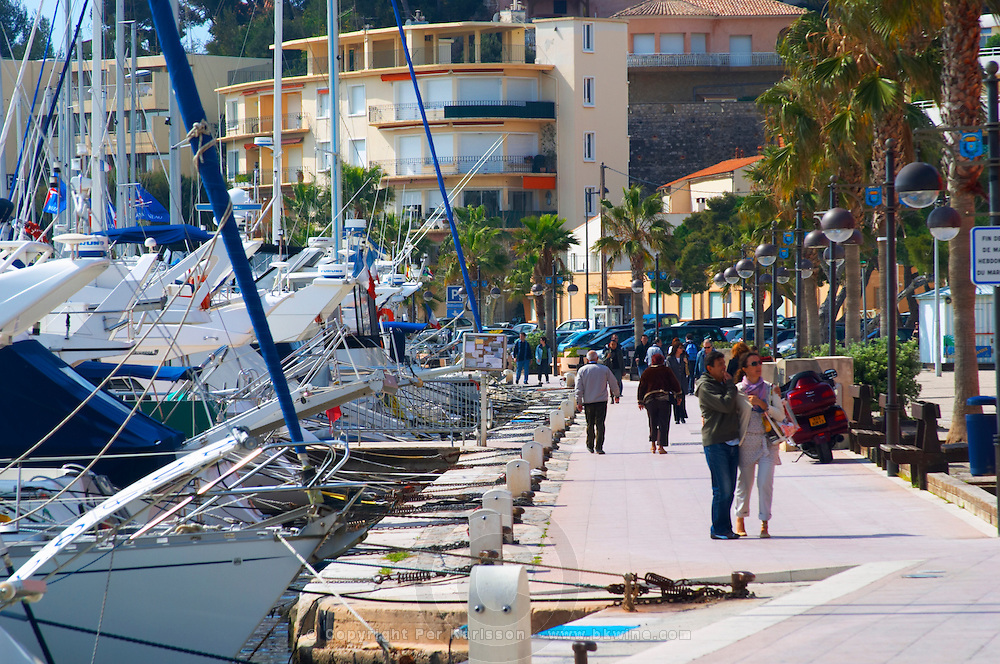The harbour with boats and buildings along the water in Bandol. White motor yachts. People walking along the key Bandol Cote d'Azur Var France