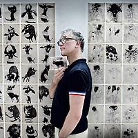 """Nederland, Amsterdam , 16 augustus 2010..Illustrator voor het Parool en tekenaar Paul van der Steen..Paul van der Steen kenden we al als STEEN van karikaturen in krant (Het Parool) en tijdschriften (Opzij, Wordt Vervolgd, VARA TV-Magazine etc.). Sinds een jaar of twee heeft hij een nieuwe, totaal vrije, innerlijk bezielde stijl van tekenen gevonden. De grote vodou-tentoonstelling """"Kunst en mystiek uit Haïti"""", in 2008-2009 in het Tropenmuseum, vormde de inspiratie. Deze vrijere tekeningen waren nog niet eerder te zien in een expositie. RETORT ART SPACE bijt trots het spits af..Drawing artist and illustrator Paul van der Steen and his exhibition."""