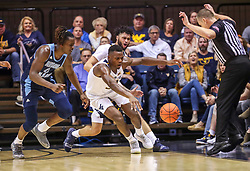 Dec 1, 2019; Morgantown, WV, USA; West Virginia Mountaineers forward Oscar Tshiebwe (34) and Rhode Island Rams forward Jermaine Harris (0) dive after a loose ball during the second half at WVU Coliseum. Mandatory Credit: Ben Queen-USA TODAY Sports