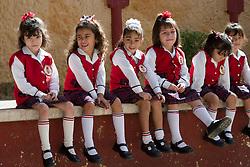 North America, Mexico, Yucatan, Valladolid, girls in school uniforms sitting on wall