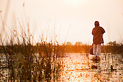 People living in the Okavango Delta often travel by Mokoro, a dug out wooden canoe. Near Seronga, Botswana. The Polers Trust is a community initiative offering tours to tourists.