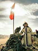 Reaching the top of the hill overlooking the Mongolian steppe and preparing to release an eagle.<br /> <br /> Eagle Hunting festival in Western Mongolia, in the province of Bayan Olgii. Mongolian and Kazak eagle hunters come to compete for 2 days at this yearly gathering. Mongolia