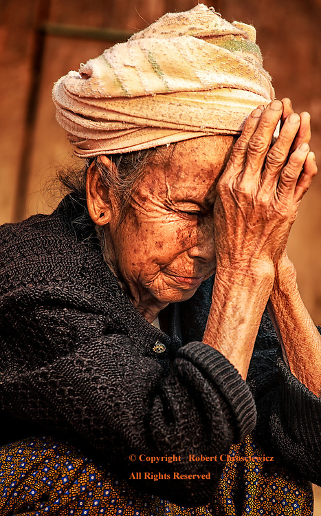 Despondent: An elderly despondent woman squats as if in prayer, in front of her ramshackle hut, Muang Sing Lao.