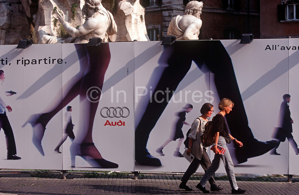 Two women walk past a billboard for car maker Audi in Piazza Navona, on 3rd November 1999, in Rome Italy.