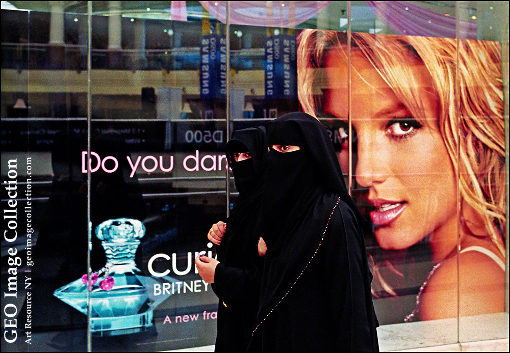 """Arab women in traditional head coverings and long smock-like cloaks -- drawn over usually attractive and colorful dresses to preserve modesty in public -- walk past a picture of pop singer Britney Spears in City Centre Shopping Mall in Dubai.  The picture of Ms. Spears was posted in the window of a perfume store to promote a line of fragrances that use Ms. Spear's name. The head covering is called a """"niqab,"""" which  covers the face entirely with an opening for the eyes.  The black gown known as an """"abaya."""""""