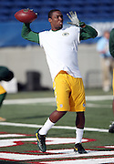 An unidentified Green Bay Packers player stands with cleats on the end zone painted surface of the field turf as he throws a pass while warming up before the 2016 NFL Pro Football Hall of Fame preseason football game against the Indianapolis Colts on Sunday, Aug. 7, 2016 in Canton, Ohio. The game was canceled for player safety reasons due to the condition of the paint on the turf field. (©Paul Anthony Spinelli)