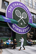 A waiter brings drinks beneath the logo for the Lawn Tennis Associations LTA Wimbledon tennis championship which appears large on the exterior facade of style retailer, Ralph Lauren in Bond Street, on 8th July 2021, in London, England.