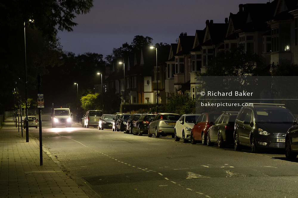In the first light of dawn, a van drives with headlights on past parked cars in a residential suburban street in south London, on 17th September 2020, in London, England.
