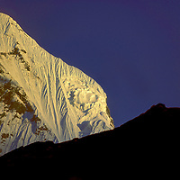 The shoulder of Machhapuchhare Peak bathed in sunset above the Annapurna Sanctuary Nepal.