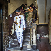 On his way to the wedding venue, the Parsi groom wears the traditional Parsi dagli and feta a white kurta like garment and a black cap. The bride will wear a white, ornate wedding saree given by her parents. The visiting entourage from the groom-to-be's family consists of five to seven women who will give the bride-to-be a gift of silver coins placed in a red brocaded bag. They may carry a sace or ses,  the Zoroastrian Ceremonial Tray, with them.