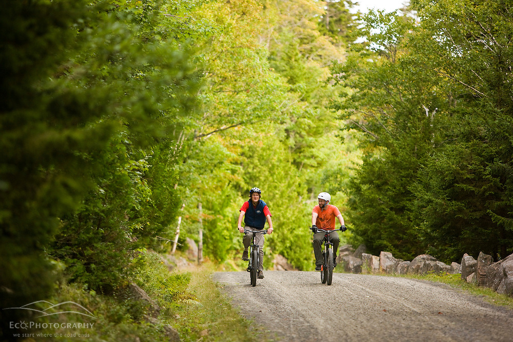 Two men biking on a carriage road near Jordan Pond in Maine's Acadia National Park.