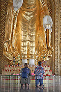 Visitors kneel in prayer inside the Dhammikarama Burmese Buddhist Temple located on Penang, Malaysia.