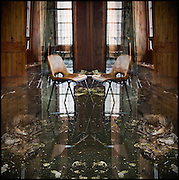Mirror image of chair in flooded corridor