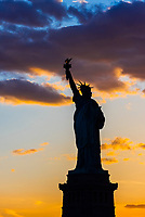 Statue of Liberty silhouetted at sunset, New York Harbor, New York, New York USA.