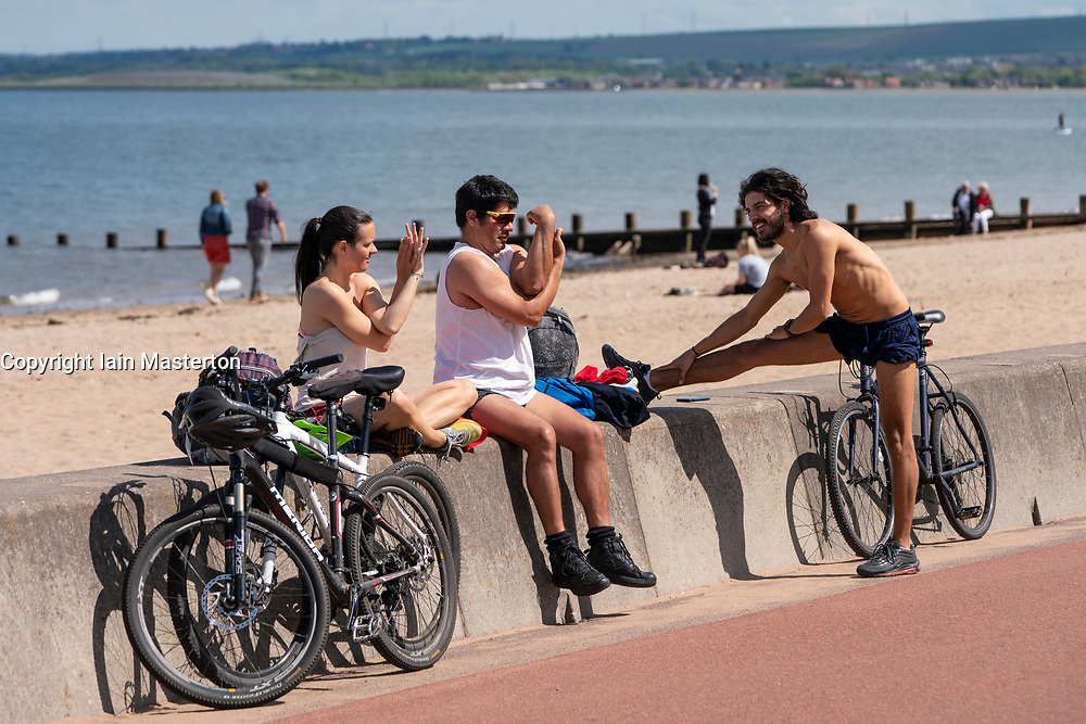 Portobello, Scotland, UK. 8 May 2020. Images from Friday afternoon during Covid-19 lockdown on promenade at Portobello. Promenade and beach were busier than in recent weeks due to warm sunny weather and the fact that several cafes and takeaway food shops are now open. Police patrols were low key. Pictured; Young people relax on sea wall in sunshine. Iain Masterton/Alamy Live News