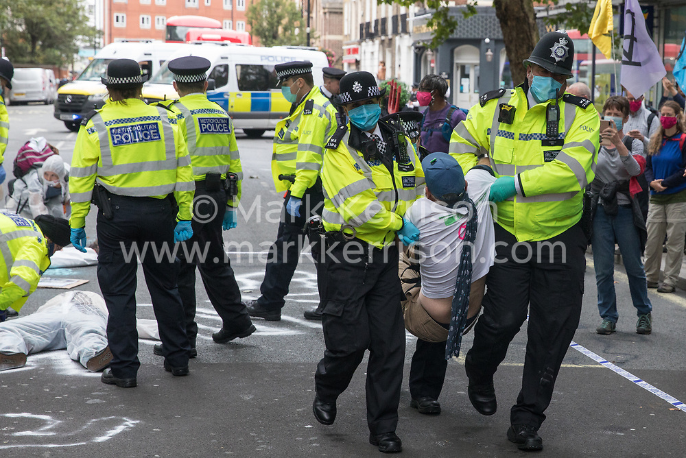 London, UK. 3rd September, 2020. Metropolitan Police officers arrest a climate activist from Extinction Rebellion who had occupied the street outside the Department of Transport in protest against roadbuilding. Extinction Rebellion activists are attending a series of September Rebellion protests around the UK to call on politicians to back the Climate and Ecological Emergency Bill (CEE Bill) which requires, among other measures, a serious plan to deal with the UK's share of emissions and to halt critical rises in global temperatures and for ordinary people to be involved in future environmental planning by means of a Citizens' Assembly.