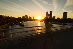 © Licensed to London News Pictures. 24/09/2018. London, UK. A woman walks across Waterloo Bridge during sunrise on the River Thames during cold but sunny weather this morning.  Photo credit: Vickie Flores/LNP