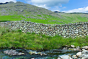 Drystone wall and mountain stream at Hard Knott Pass in the Lake District National Park, Cumbria, UK