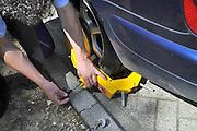 Nederland, Nijmegen, 16-8-2011Parkeerwachter maakt wielklem op wiel van mijn auto los.Foto: Flip Franssen/Hollandse Hoogte
