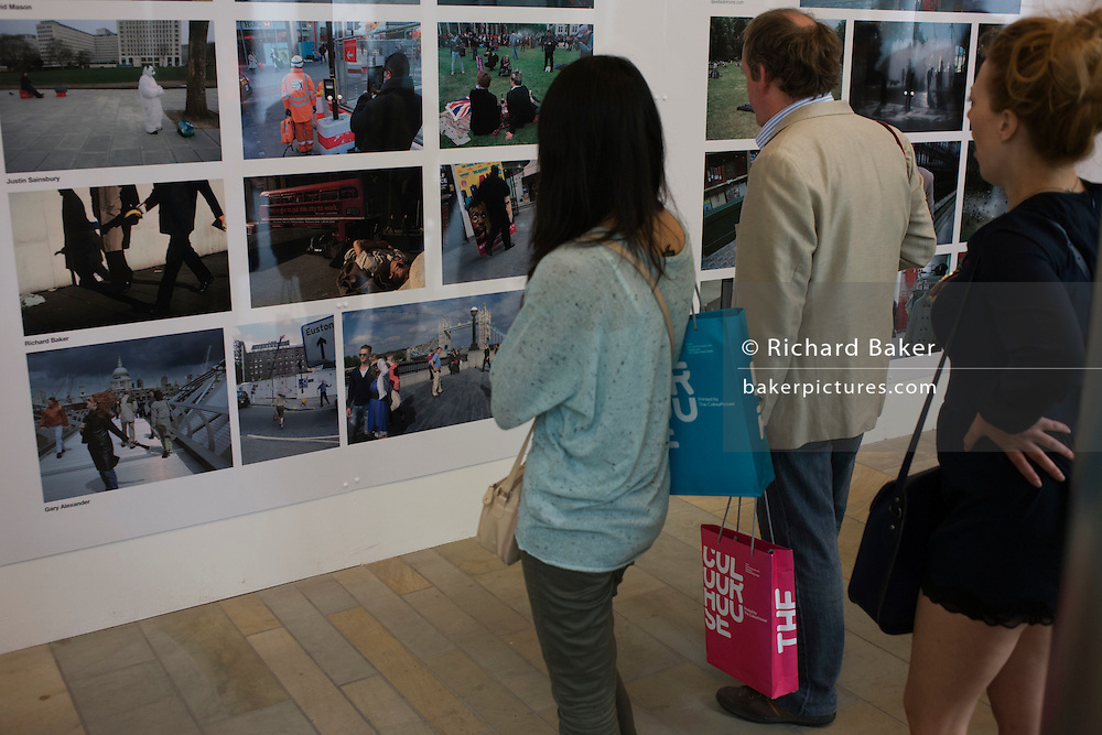 Visitors to the Contemporary London Street Photography show at King's Cross station.