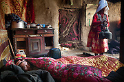 Early morning inside Mustafa Qol's house. Like often, women are at work while men are still sleeping. Mustafa Qol's wife (Mamalai sister) working while Mustafa Qol's brother sleeps. .At the camp of Tash Seri (Mustafa Qol's camp)...Trekking through the high altitude plateau of the Little Pamir mountains, where the Afghan Kyrgyz community live all year, on the borders of China, Tajikistan and Pakistan.