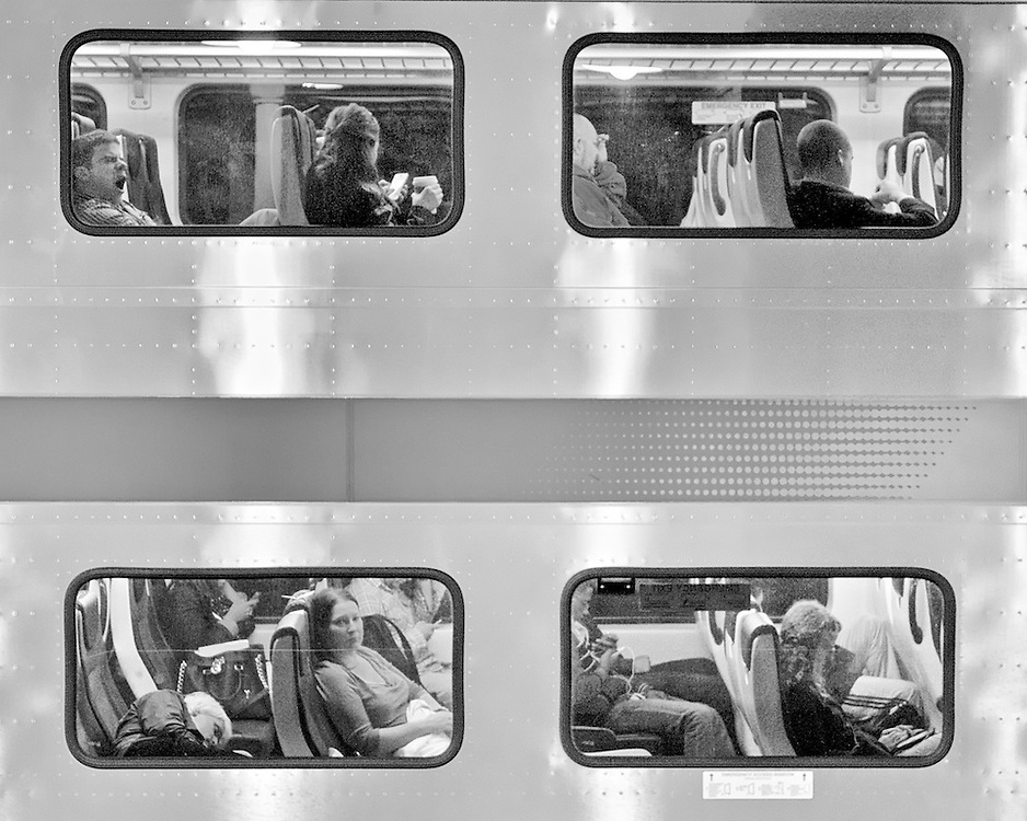 As a commuter who observes passing trains at my departing and arriving stations, I've found it interesting to peer through the windows and observe people and their body language during their own commute. People seem to let down their guard behind glass, whether it's in a car, train, or restaurant, and act more naturally without regard to the person with the camera aimed their way.<br /> <br /> Shooting various trains, I quickly discovered that NJ Transit's new double deck cars offer four windows in a compact area, which allowed for more individual vignettes. These individual vignettes can be very interesting in themselves, but when multiplied by 4 scenes, they created a more telling story of the commuter experience.<br /> <br /> I photographed from the opposite platform and shot after dark as it allowed a good view into the car interior. I shot many images over a 6-week span and selected this one to send to the CRPA Awards competition, as I liked the various poses as well as the young women starring back at me….a rare engagement with my subject commuter.
