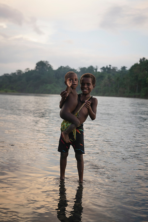 Stesie holds a toddler named Yagang at sunset while standing in the Clay River in the village of Likan, located in East Sepik Province in Papua New Guinea.<br /><br />(June 24, 2019)