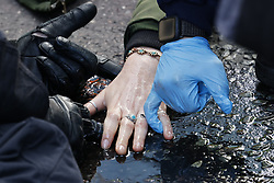 © Licensed to London News Pictures. 25/10/2021. London, UK. Police work to unglue an Insulate Britain activist as she lies on the road on Bishopsgate in the City of London. The group have restarted their actions to block motorways and major roads causing disruption in the week before the COP26 climate meeting in Glasgow on 31/10/2021. Photo credit: Peter Macdiarmid/LNP