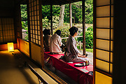 every day Street scene in Japan. Japanese women in traditional Kimono drinking tea