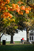 Leslie Jaworski passes in front of the Joe Rosenfield '25 Center on bicycle as Fall colors begin to abound on Central Campus.