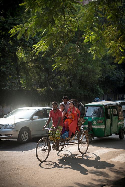Dhaka, Bangladesh - November 1, 2017: A family rides in a bicycle rickshaw on a street in Dhaka, Bangladesh.