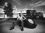 An african-american man sits down with a giant tire from his 18 wheeler truck.