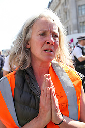 © Licensed to London News Pictures. 19/04/2019. London, UK. An environmental activist says her prayers in Oxford Circus on the fifth day of the climate change protest by the Extinction Rebellion movement group. Photo credit: Dinendra Haria/LNP