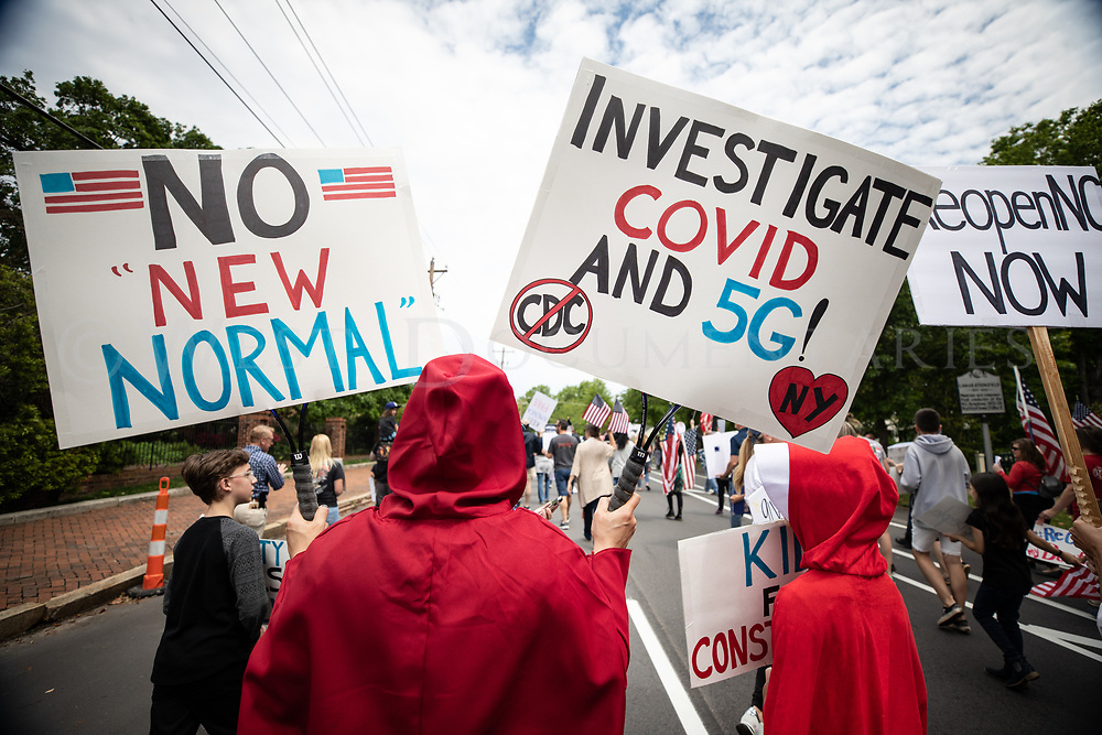 A mother and her daughter, dressed as the characters from the Netflix series, Handmaid's Tale, march down West Jones Street, Raleigh, N.C., during the ReOpenNC Rally on April 21, 2020.