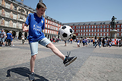 A Leicester City fan plays football in Plaza Mayor ahead of the game