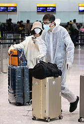 """© Licensed to London News Pictures. 17/03/2020. London, UK. Passengers wear face masks and one wears a protective suit as they check in at Heathrow Airport's Terminal Four. The government have advised the public that they should avoid """"non-essential"""" travel and contact with others to curb the spread of the coronavirus. Photo credit: Peter Macdiarmid/LNP"""