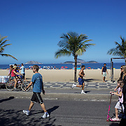 Walkers exercise early on Sunday morning at Ipanema Beach. On Sunday's the main roads along the beaches of Copacabana, Leblon and Ipanema are closed to traffic bringing out thousands of people of all ages to walk, run, jog, ride, skateboard and cycle more than 10 km of beachside roadway. Rio de Janeiro,  Brazil. 4th July 2010. Photo Tim Clayton....