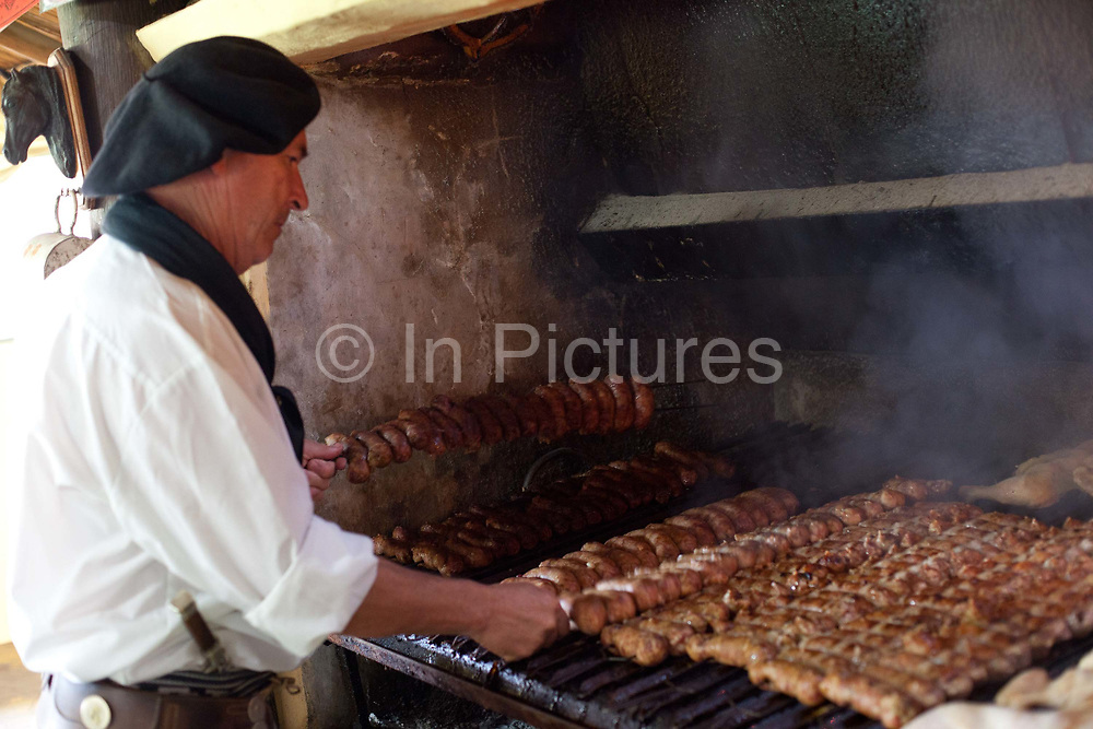 A gaucho cooking sausages on a parilla at an Estancia in Lujan, Buenos Aires, Argentina.