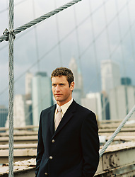 Man in a suit standing on the Brooklyn Bridge in New York City