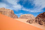 Red sand dunes and high sandstone cliffs in the desert of Wadi Rum, Jordan.