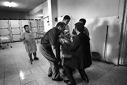 Hassan Kange collapses in grief after identifying the body of his son Ahmad Kange, 13, who died the previous night when an apartment building was hit by an Israeli raid, in Beirut, Lebanon, Aug. 8, 2006. <br /> Ahmad left his home, one block from the scene, to get an ice cream cone when he was killed. The attack, which took place in the residential neighborhood of Chiyah, killed more than two dozen people and wounded scores more. The Kange family were not Hezbollah supporters but Amal supporters, the rival Shia group in Lebanon.
