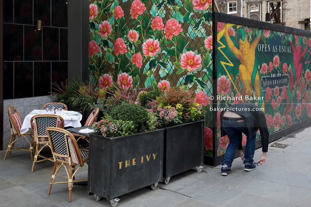 A man stoops to adjust a shoelace in front of temporary construction hoarding in a West End street, on 7th March 2019, in London, England.
