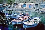 Oar boats moor in emerald water at Thirasia Island (or Therasia), Greece.